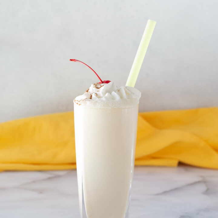 close up of banana milkshake with whipped cream and a cherry on top