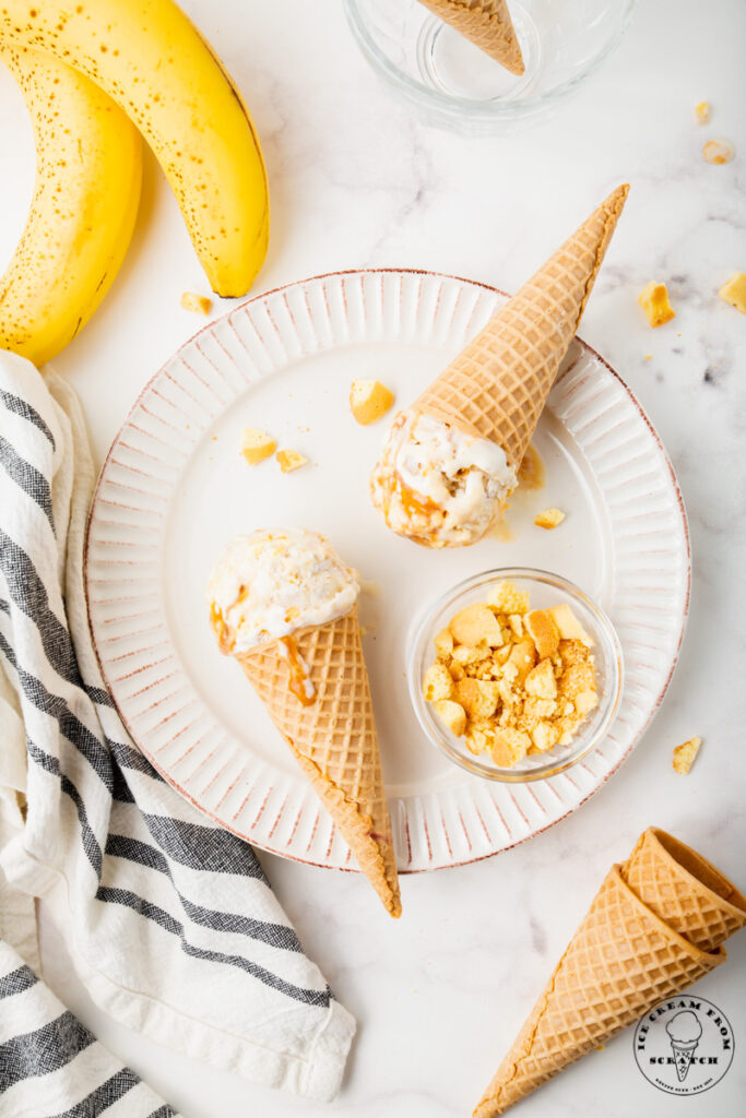 a white scalloped plate holding two sugar cones of banoffee pie ice cream and a dish of crushed vanilla wafers.