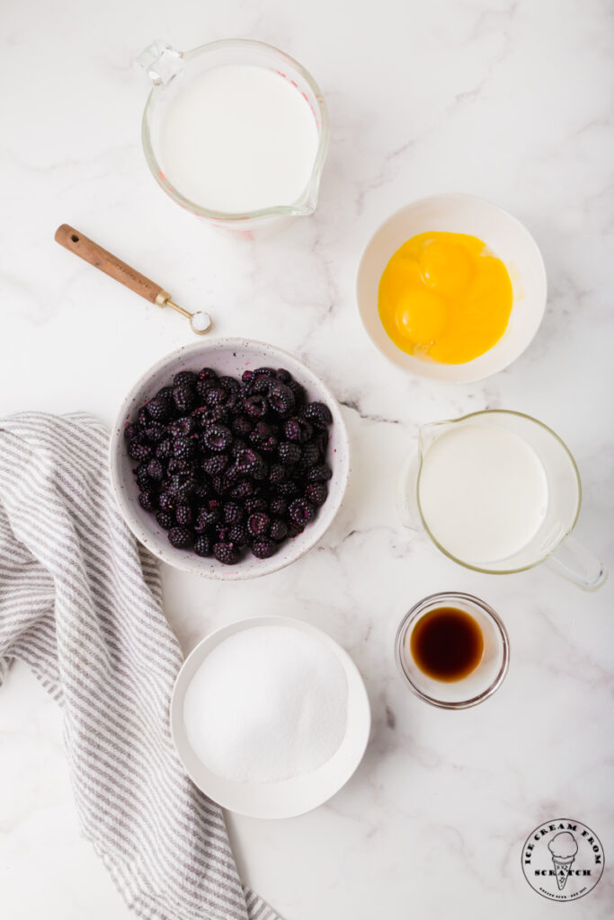 Ingredients for black raspberry ice cream, each in separate bowls on a marble counter