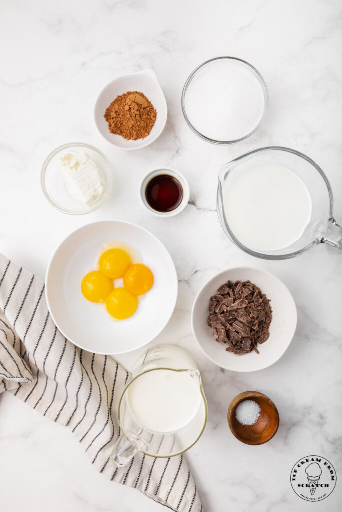 ingredients needed to make french silk ice cream, each in separate bowls on a marble countertop