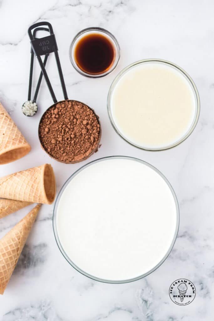 Ingredients for no churn chocolate ice cream in separate bowls on a marble counter, along with sugar cones.