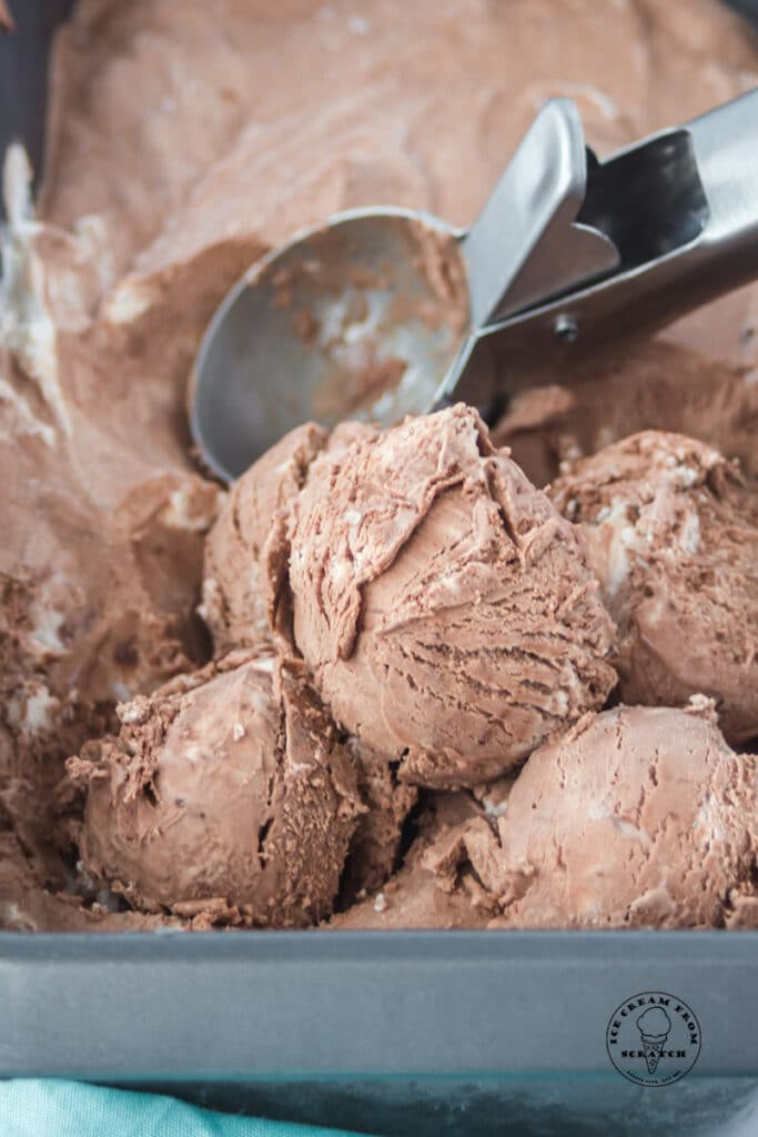 a pan of chocolate ice cream being scooped with a silver ice cream scoop