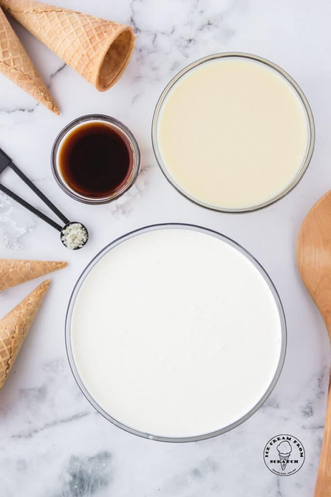 Ingredients needed to make no churn vanilla ice cream in separate bowls on a marble counter along with sugar cones.