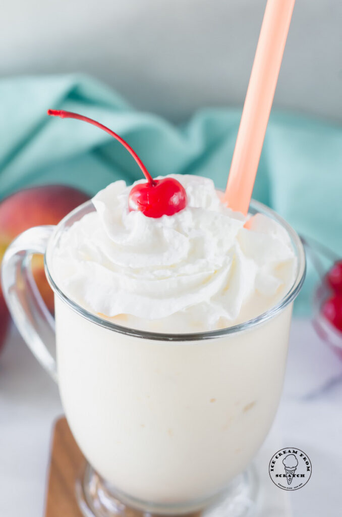 close up of a peach milkshake in a clear glass topped with a cherry