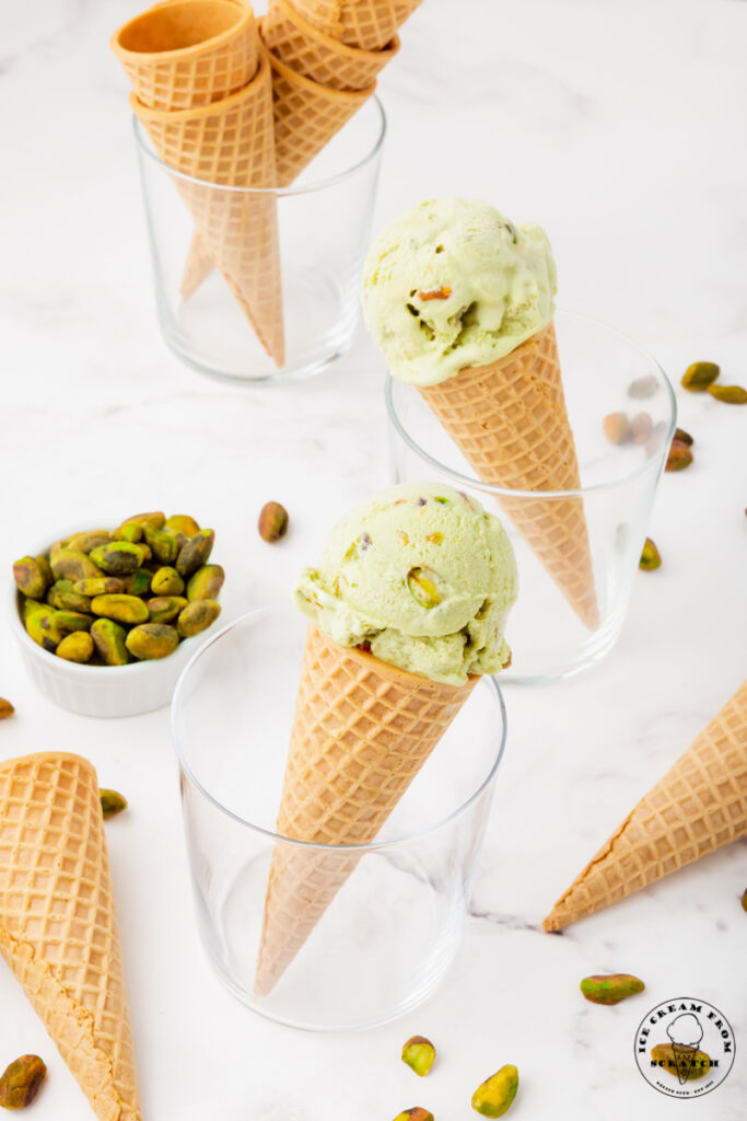 three glasses, two with cones of pistachio ice cream in them. One with a stack of sugar cones. Glasses are surrounded by pistachios
