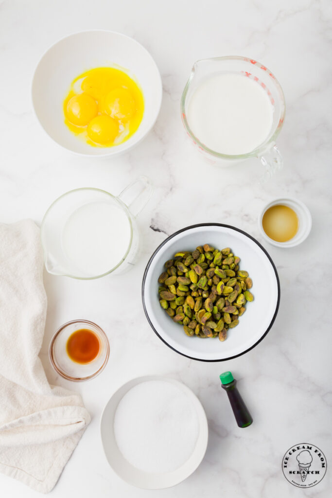 Ingredients needed for pistachio ice cream, each in separate bowls on a marble countertop.