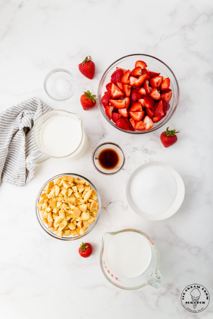 Ingredients needed for strawberry shortcake ice cream, each in separate bowls on a marble countertop