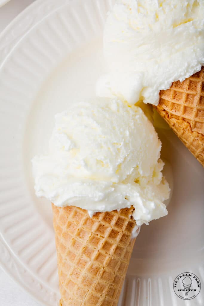 closeup view of two sugar cones of sweet cream ice cream on a white plate.