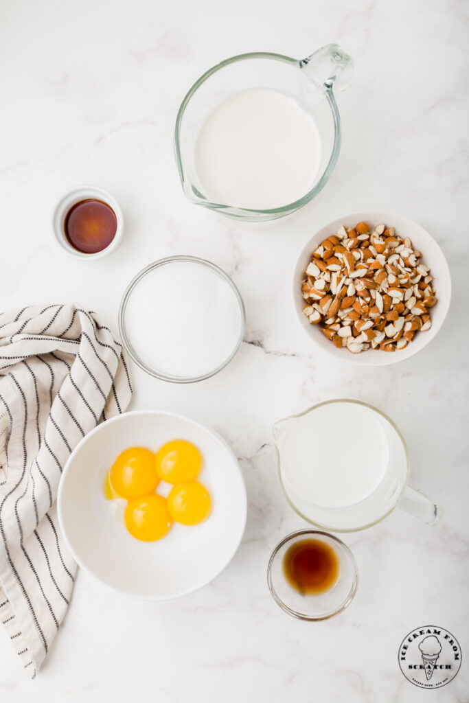 Ingredients for Toasted almond ice cream, each in separate bowls on a marble countertop