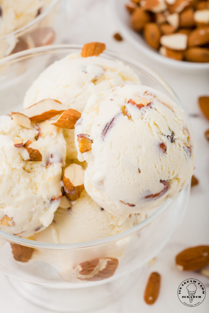 a glass ice cream dish filled with almond ice cream.