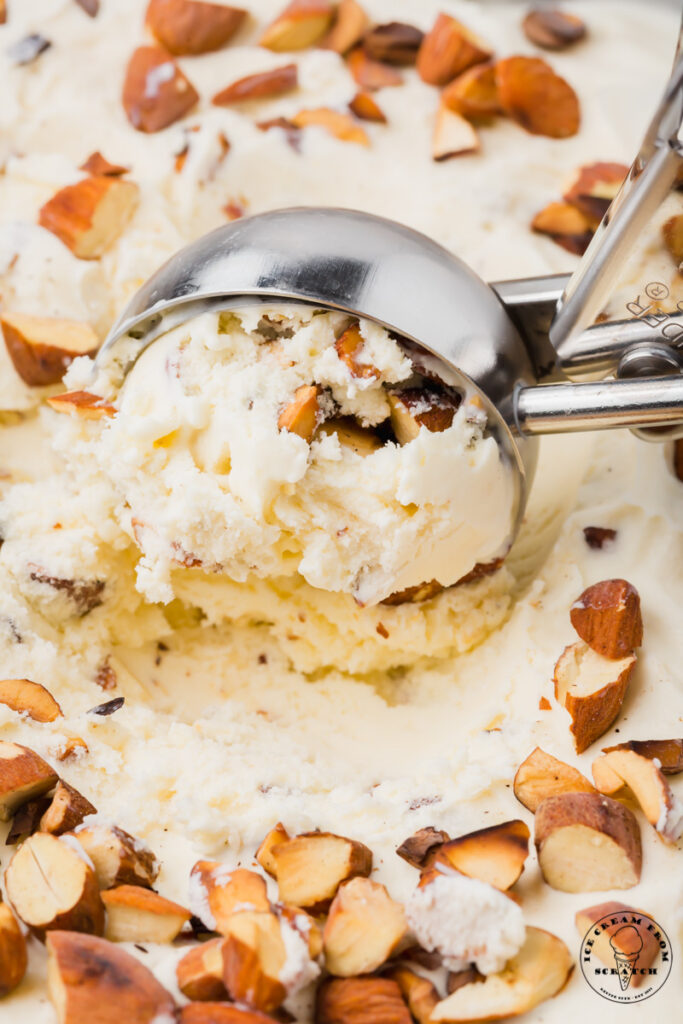 almond ice cream being scooped with a metal ice cream scoop