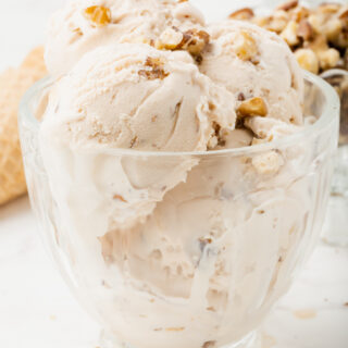 black walnut ice cream, multiple scoops in a glass ice cream dish, topped with chopped walnuts.