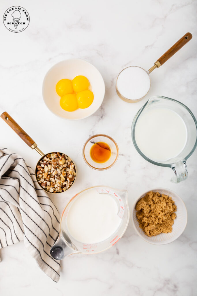 ingredients needed for making black walnut ice cream, including nuts, sugar, milk, eggs, and brown sugar, each in separate dishes on a marble countertop