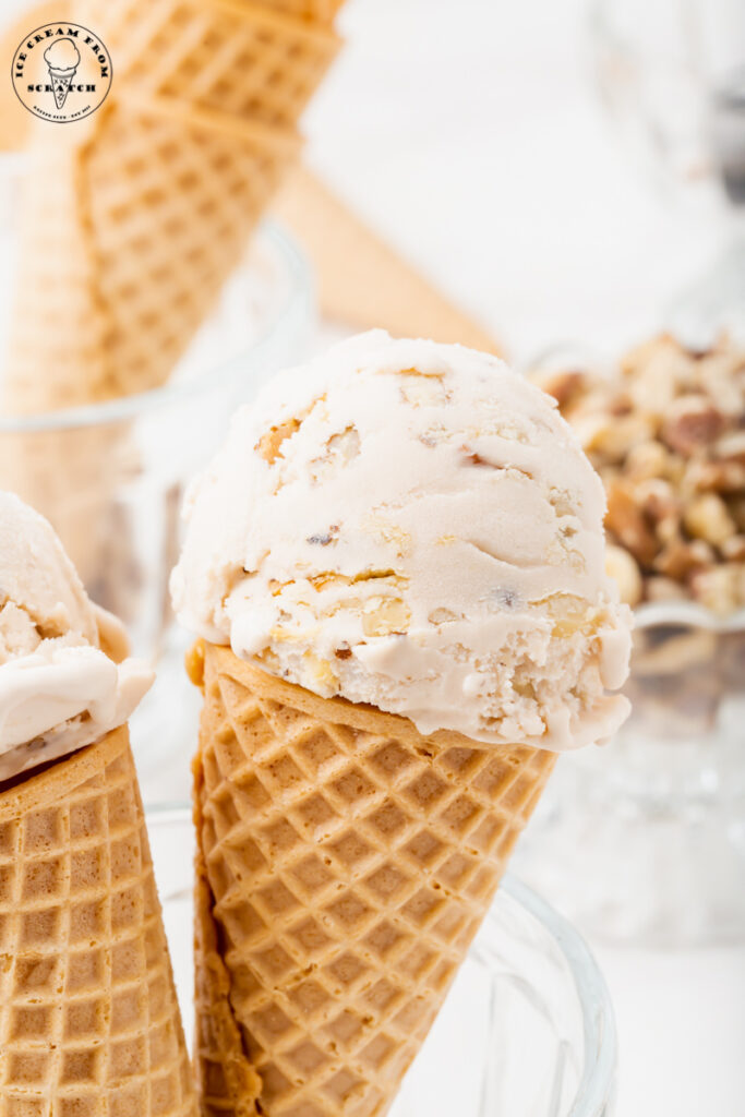 two sugar cones topped with a scoop of walnut ice cream, propped up in a glass dish.