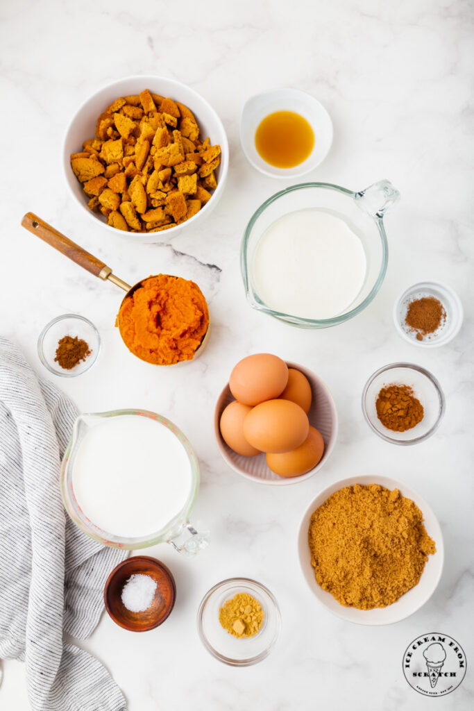 top down view of all of the ingredient needed to make pumpkin pie ice cream, each in separate white and glass bowls, all set on a marble countertop