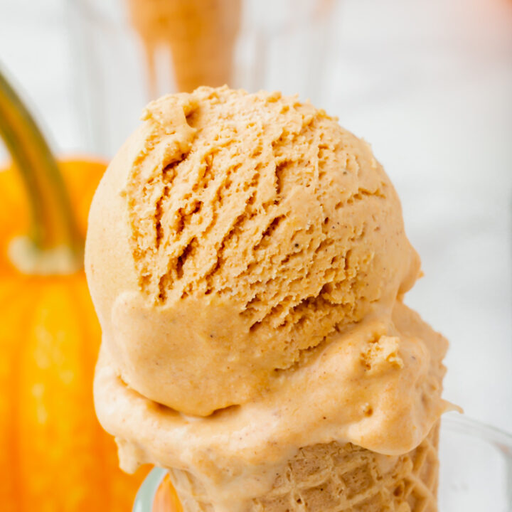 a sugar cone with a scoop of pumpkin spice ice cream, propped up in a glass. There is a pumpkin in the background.